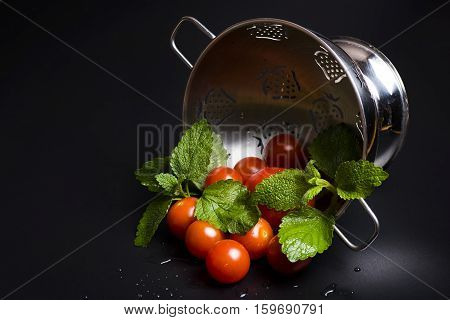 Fresh tomatoes and lemon balm in a metal strainer on a black background