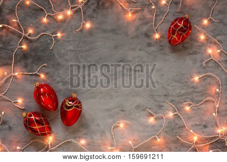 Christmas lights frame on dark grey stone background with red Christmas ornaments fir cones, copyspace