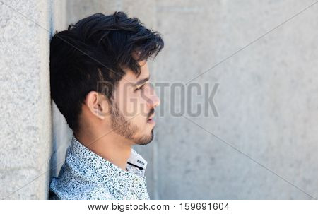 Hipster with beard and fashionable clothes looking sideways outdoor in the summer