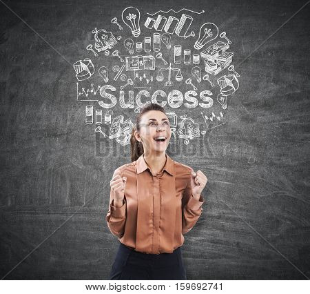 Portrait of an ecstatic businesswoman with an open mouth standing near a blackboard with a success sketch on it