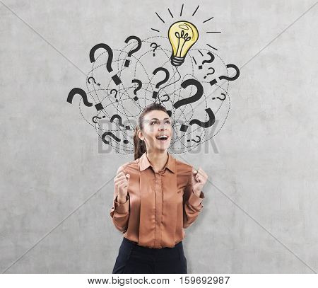 Portrait of an ecstatic woman in a brown blouse standing near a concrete wall with a glowing light bulb and question mark sketches
