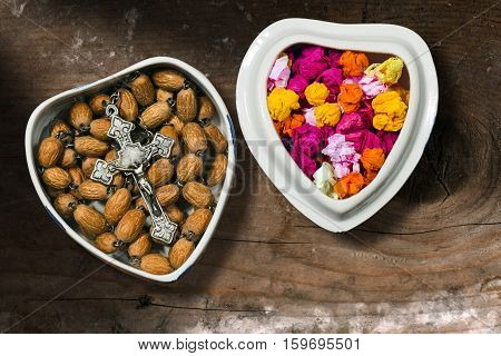 Small ceramic box heart shaped with an old silver crucifix and rosary with wooden beads and pieces of colored paper