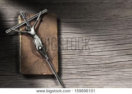 Silver crucifix on an aged Holy Bible. On a pine wood background with dark shadows