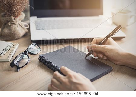 woman writing on notebook at workplace. Vintage tone
