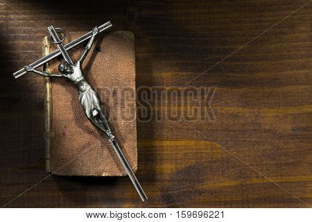 Silver crucifix on an aged Holy Bible on a wooden table with dark shadows