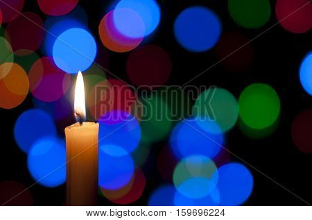 A white candle on a Christmas light background
