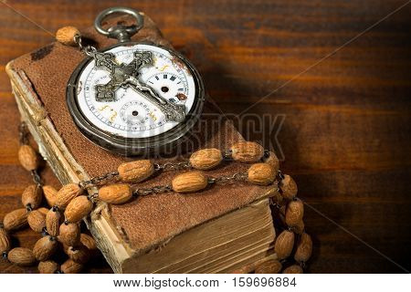 Time to Pray - Old pocket watch with a vintage silver crucifix and a rosary with wooden beads on an old Holy Bible