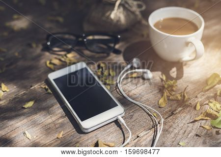 Cup of coffee and cellphone on wooden table in the garden Vintage tone