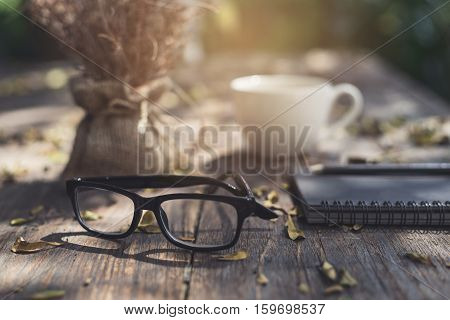 Notebook with cup of coffee and cellphone on wooden table in the garden Vintage tone