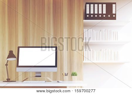 Close up of a blank computer monitor standing on an office table. There are bookshelves with book and binders on the right. 3d rendering. Mock up. Toned image
