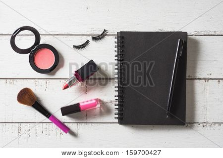 Blank notebook with Various make-up products and cosmetics on wooden table Top view