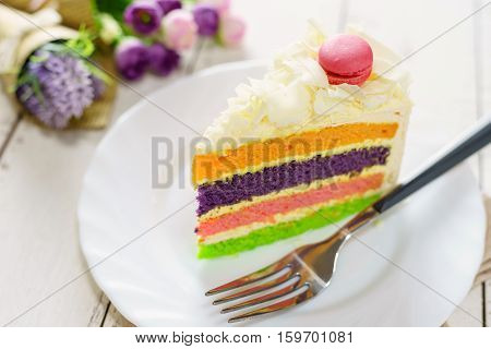 Fancy cake with macaroon on top and cup of tea on white wooden table