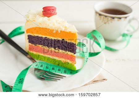 Fancy cake with measure tape and cup of tea on white wooden background healthy concept