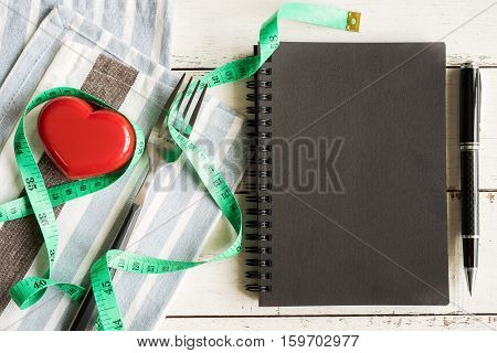 Red heart and notebook with measure tape on white wooden background healthy concept