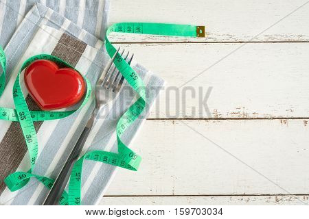 Red heart and healthy concept with measure tape on white wooden background