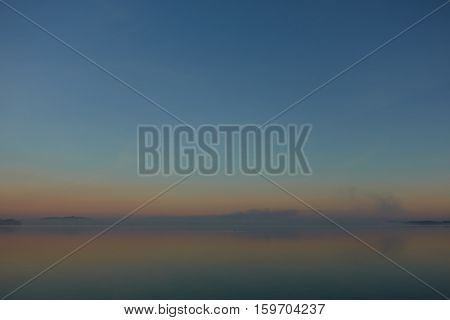 Scenic view of a foggy lake in autumn at sunset