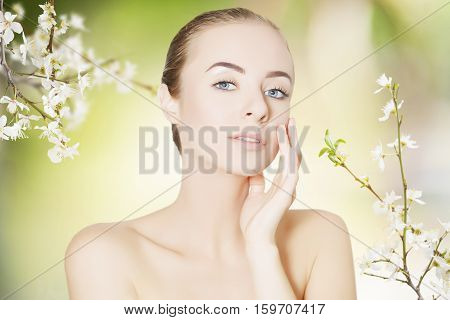 caucasian woman touching her cheek spring background