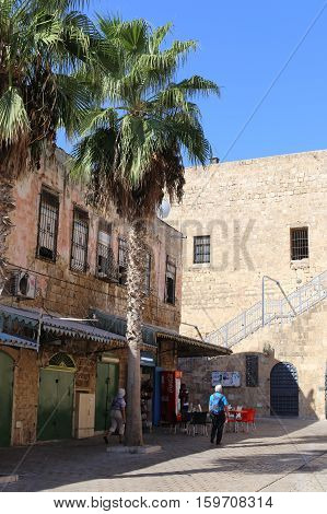 ACRE ISRAEL - CIRCA SEP 2016: Inside of an Old city Acre (Akko). Old buildings palm trees and tourists walking