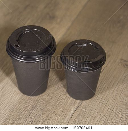 two paper Cup of black coffee on wooden background