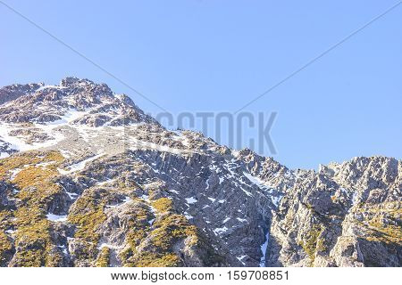 View of top mountain cook with white snow and rock texture.