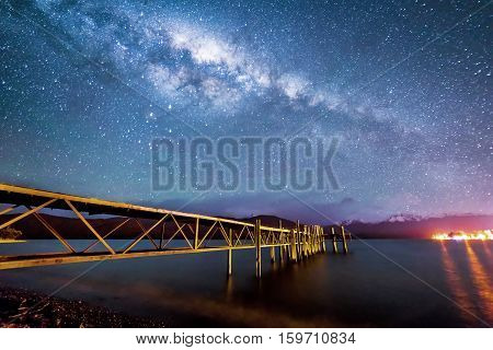 Night milkyway with wooden jetty at Te Anau New Zealand