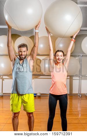 Portrait of the sports couple with fitballs in the fitness gym