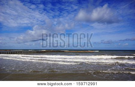 wooden breakwater at the baltic sea on a background of blue sky and the foamy water