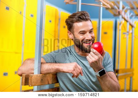Sports man eating an apple sitting after the training in the locker room of the gym. Healthy natural food for sports men