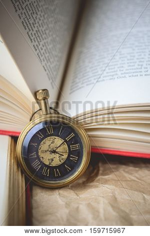 Pocket Watch with Old Book on Crumpled Paper in Vintage Tone