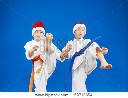 Two boys karateka are beating kick leg