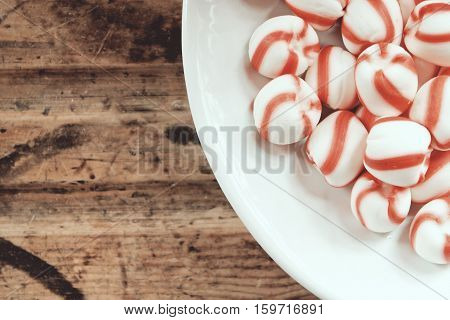 Close up of vintage peppermint candies in dish against wood table