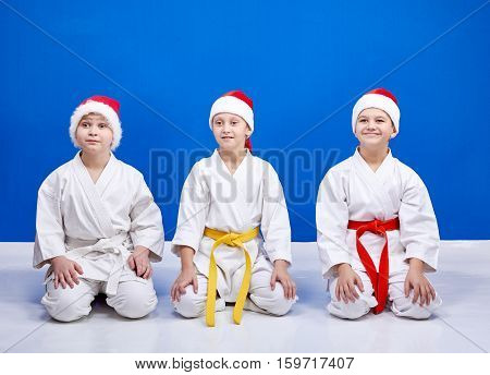Three karateka in caps of Santa Claus sitting in a karate pose