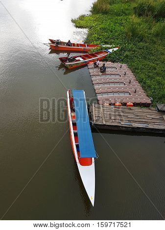 KANCHANABURI THAILAND - NOVEMBER 26: long tail boat with unidentified driver under the Bridge on the river Kwai on November 26 2016 in Kanchanaburi Thailand