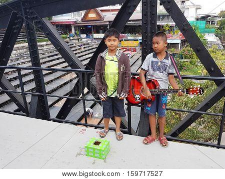 KANCHANABURI THAILAND - NOVEMBER 26: unidentified asian children playing guitar for donating on Bridge on the river Kwai on November 26 2016 in Kanchanaburi Thailand