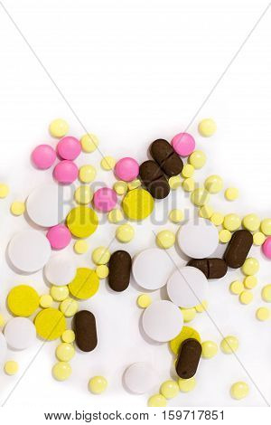 Pills scattered across. Isolated on white background.