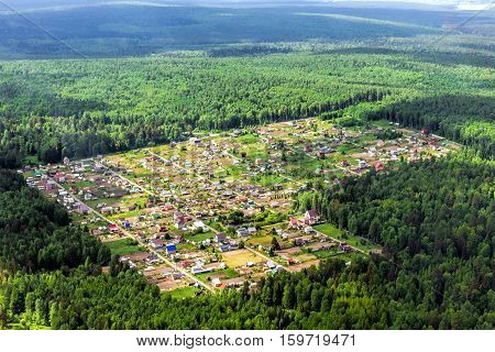 The cozy little village in the middle of the taiga forest. Airview