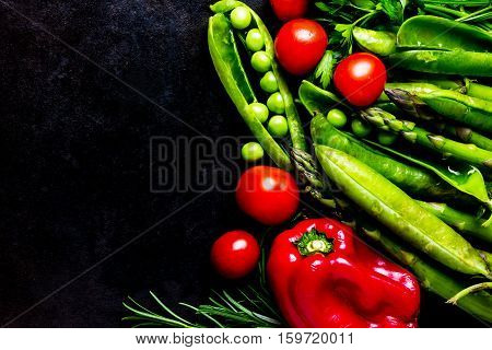 Food background - raw organic vegetables, fresh ingredients for healthily cooking on black background - bell pepper, green pea, asparagus, tomatoes, rosemary. top view. Vegetarian or healthy food