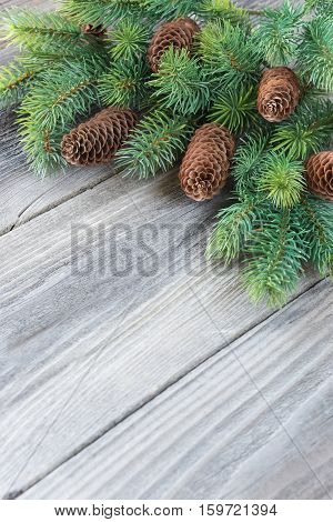 Christmas frame composed of pine cones and spruce branches on the background of old unpainted wooden boards; Christmas composition for greeting card with copy-space