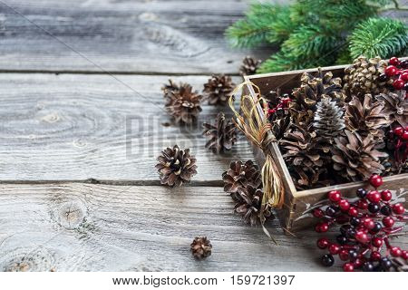Christmas decoration: full wooden box of pine cones and red holly berries and spruce branches on the background of old unpainted wooden boards; Christmas composition for greeting card websites social media business owners magazines bloggers artists etc.