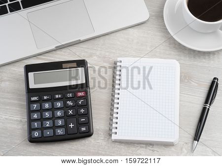 Calculator and notepad on wooden table .