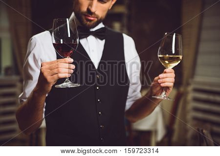 Sommelier is holding two wineglasses with red and white drink. He looking at it with attention