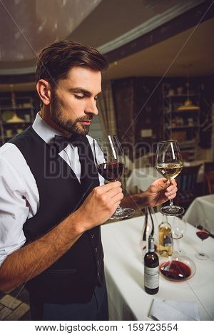 Concentrated sommelier is trying to feel smell of scarlet alcohol nectar