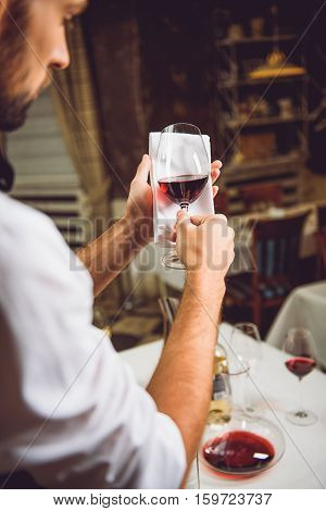 Sommelier is holding wineglass with scarlet nectar against serviette