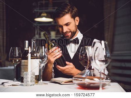 Interested man is sitting and carrying wine in hands. He fixedly gazing at nectar