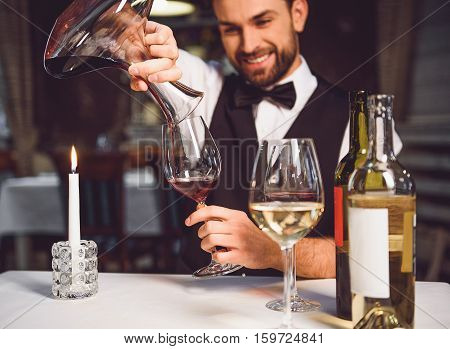 Laughing sommelier is sitting at table and poring red nectar in wineglass