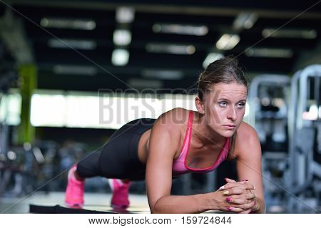 Shot of a fit young woman doing stretching workout on the gym floor. Muscular female exercising at health club.