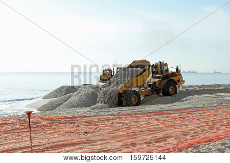Fort Lauderdale FL USA - March 3 2016: Piles of sand dumped on the beach shore replenish and widen. Large trucks restore sand on the coast expanding the beach.
