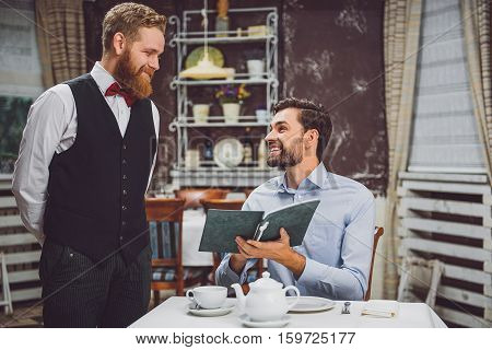 Hilarious man is sitting at table and telling his choice to standing guy. Waiter with kindly smile listening carefully poster