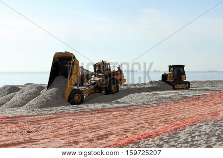 Fort Lauderdale FL USA - March 3 2016: Two dump trucks and a bulldozer work on beach nourishment on the coast. Earth moving equipment add sand to a public beach.