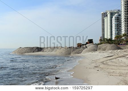 Fort Lauderdale FL USA - March 3 2016: Large sand piles distributed on the shores widening the beach. Shore beach expansion machinery spreading the sand.